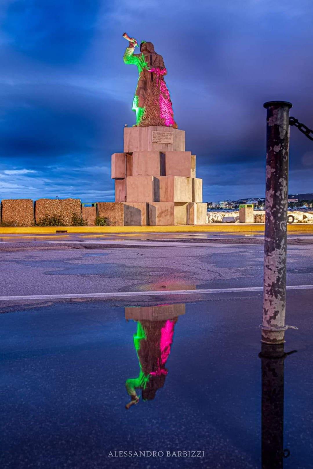 Il monumento al Pescatore illuminato metà viola e metà verde